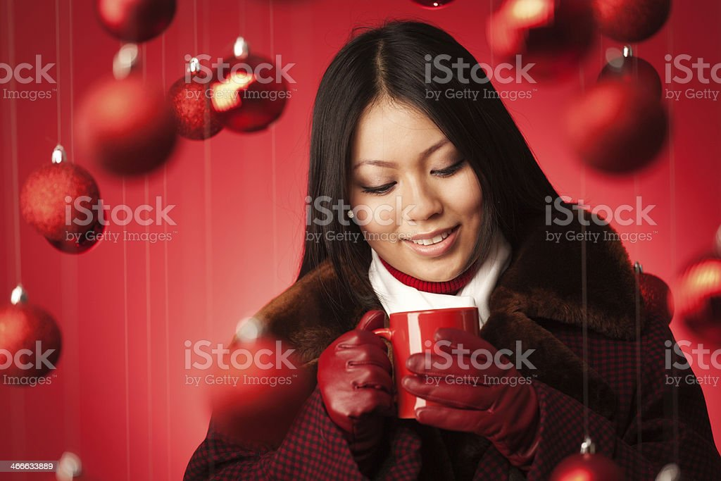 Christmas Theme Asian Model in Winter Coat and Hot Drink royalty-free stock photo