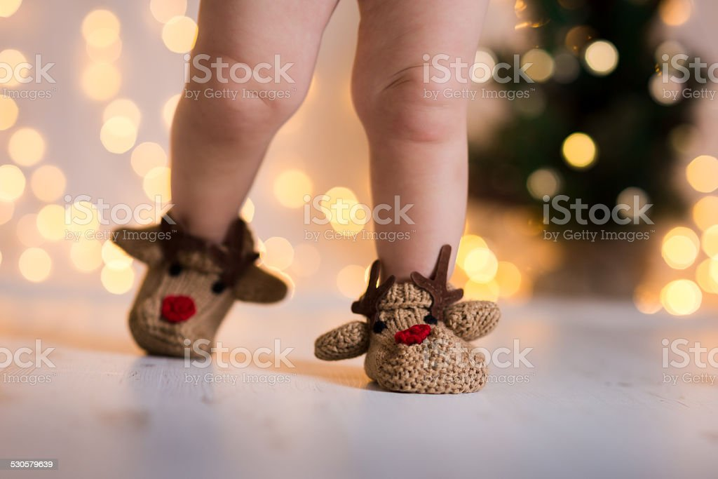 Christmas theme Baby's legs in knitted festive deer like booties stock photo