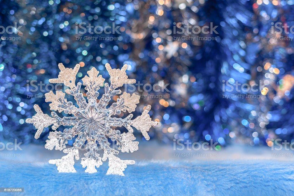 Christmas toy snowflake on sparkling bright blue bokeh background. stock photo