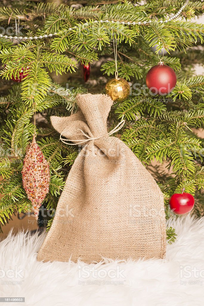 Christmas tree and burlap sack filled with gifts royalty-free stock photo