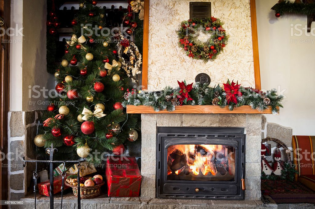 Christmas tree and burning fireplace at home stock photo