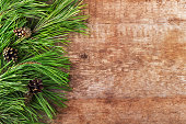Christmas tree and cones on a wooden background