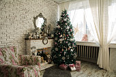 Christmas tree and fireplace with an armchair