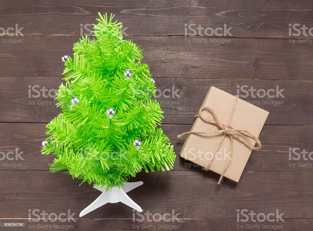 Christmas tree and gift box on on the wooden background. stock photo
