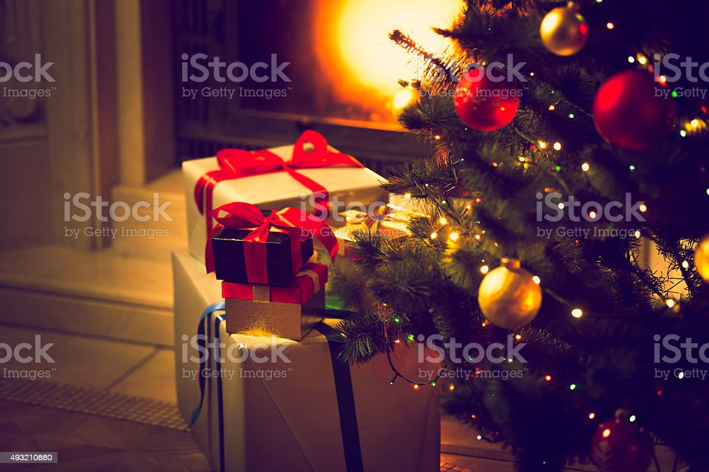 Christmas tree and gift boxes against burning fireplace stock photo