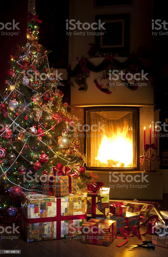 Christmas tree and gifts on background of burning fireplace royalty-free stock photo