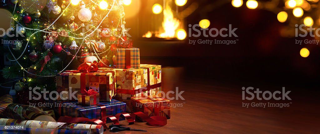 Christmas tree and holidays present on fireplace background stock photo