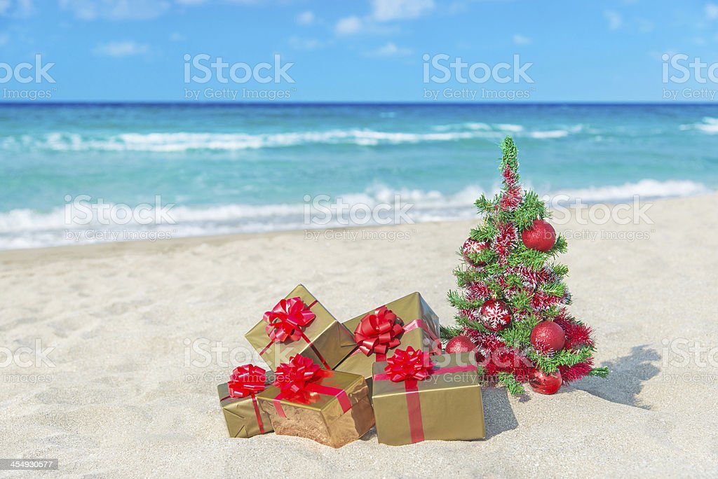 Christmas tree and many gift boxes on sea beach royalty-free stock photo