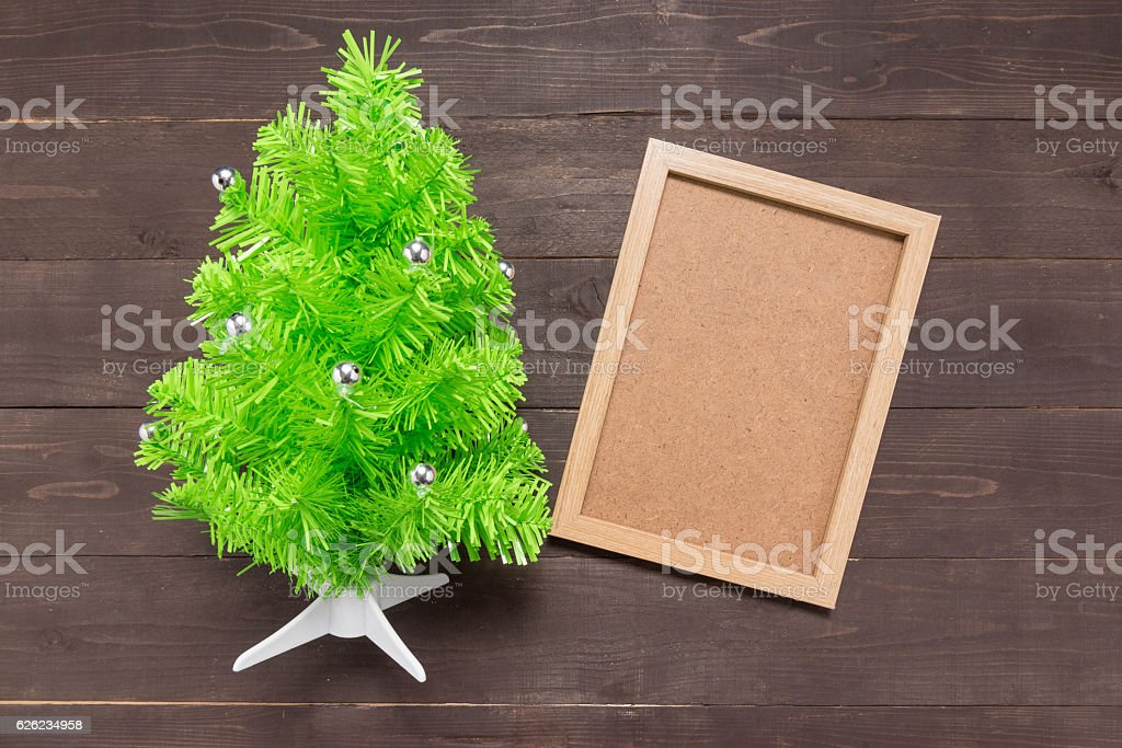 Christmas tree and picture frame are on the wooden background stock photo