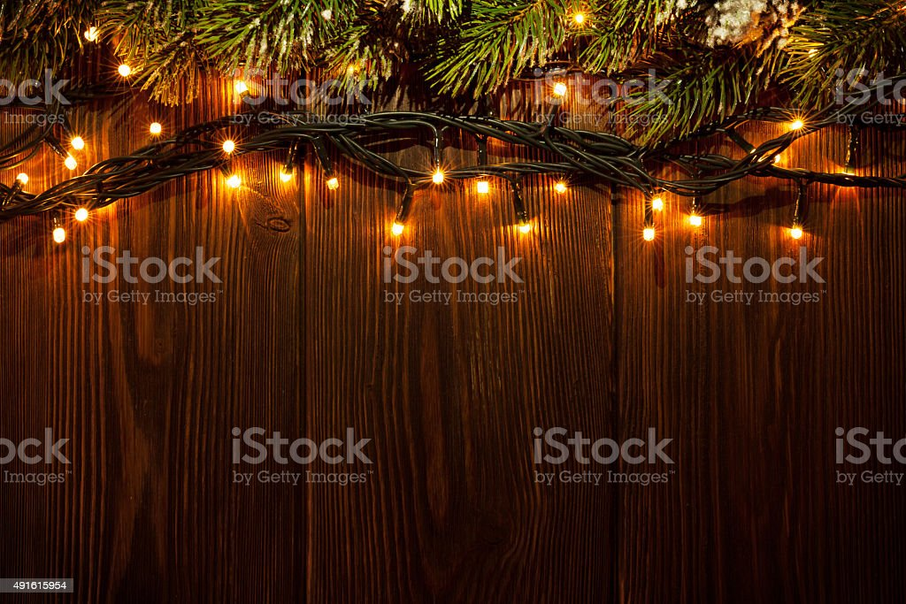 Christmas tree branch and lights on wooden background. View with copy...