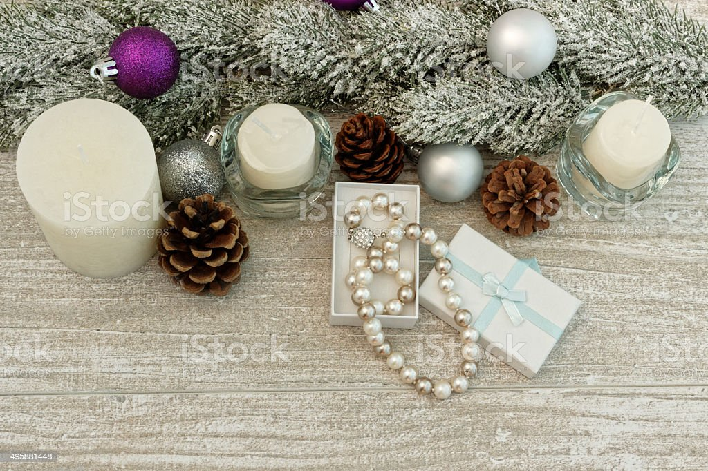 Christmas tree branches, candles and pearl necklace stock photo