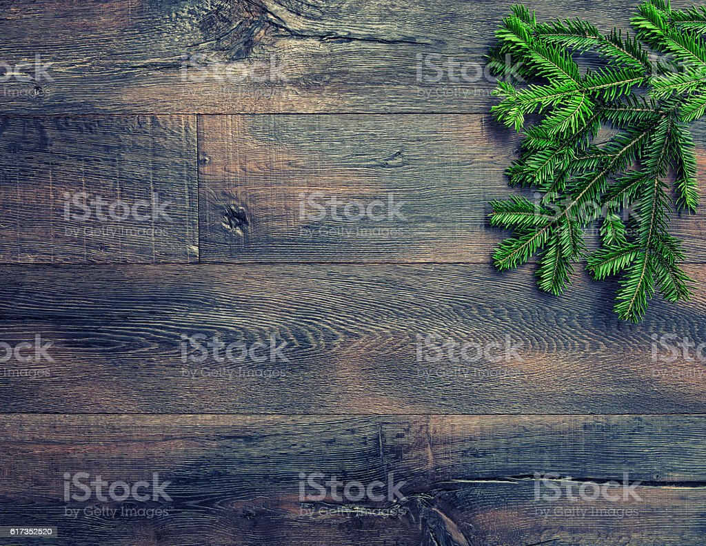 Christmas tree branches on rustic wooden texture. Vintage style stock photo
