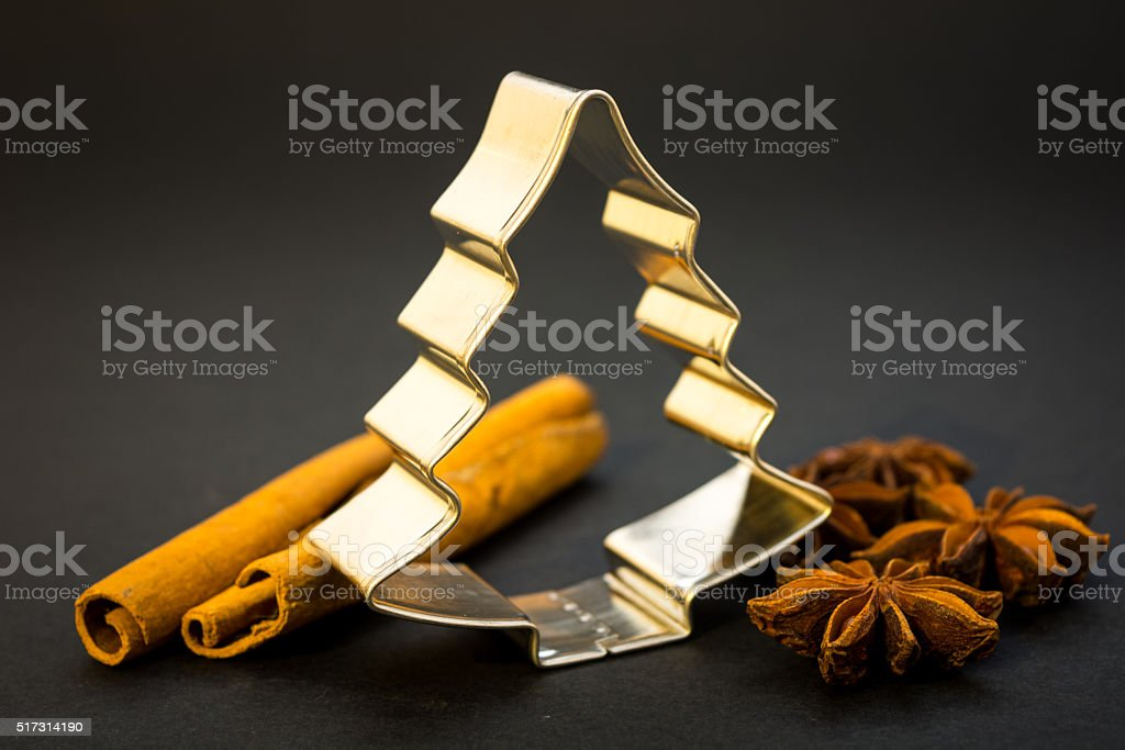 Christmas tree cookie cutter, anise stars and cinnamon sticks stock photo