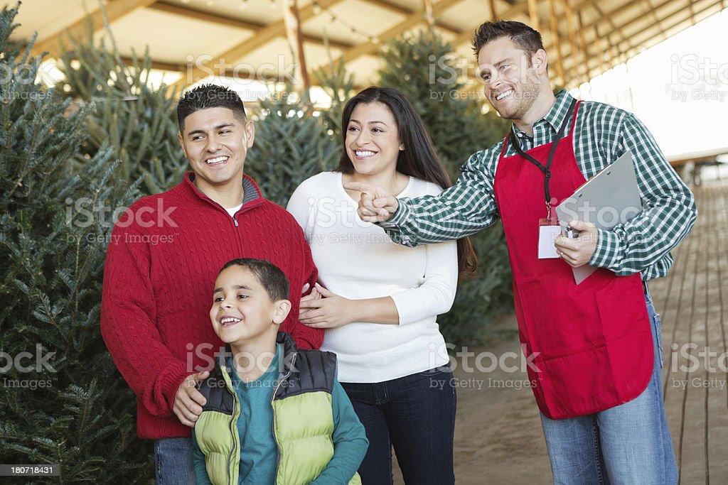 Christmas tree farm salesman assisting young Hispanic family royalty-free stock photo