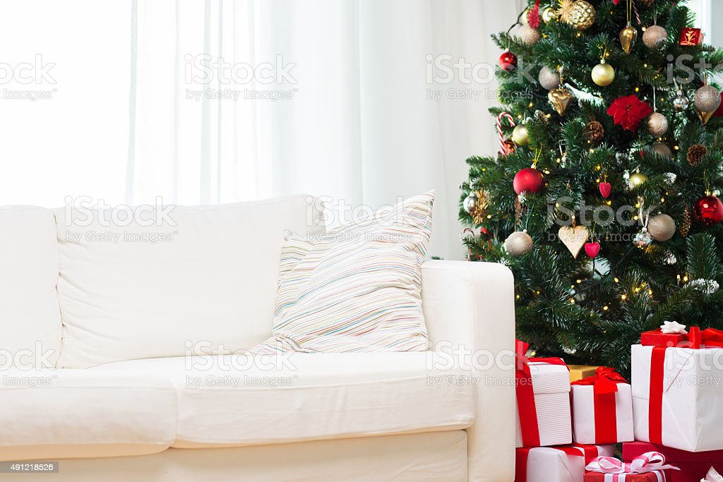 christmas tree, gift boxes and sofa at home room stock photo