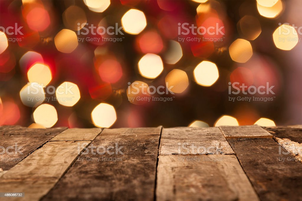 Christmas tree, holiday lights behind wooden table. Copyspace. stock photo