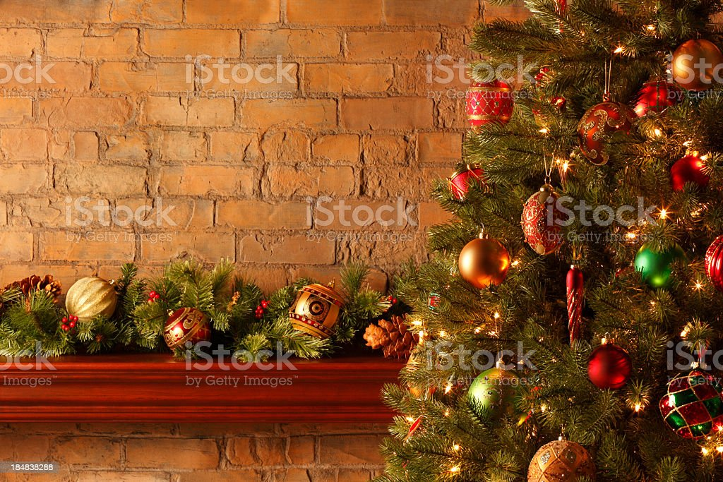 Christmas tree in front of mantel piece adorned with bough royalty-free stock photo