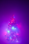 Christmas tree lights garland in frozen mist