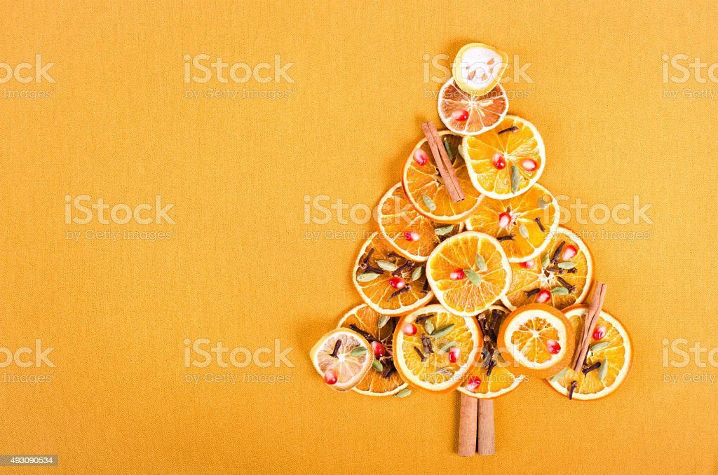 Christmas tree made of dried oranges, lemon, spices on yellow stock photo