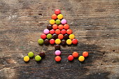 Christmas tree made with colorful candies on wooden table