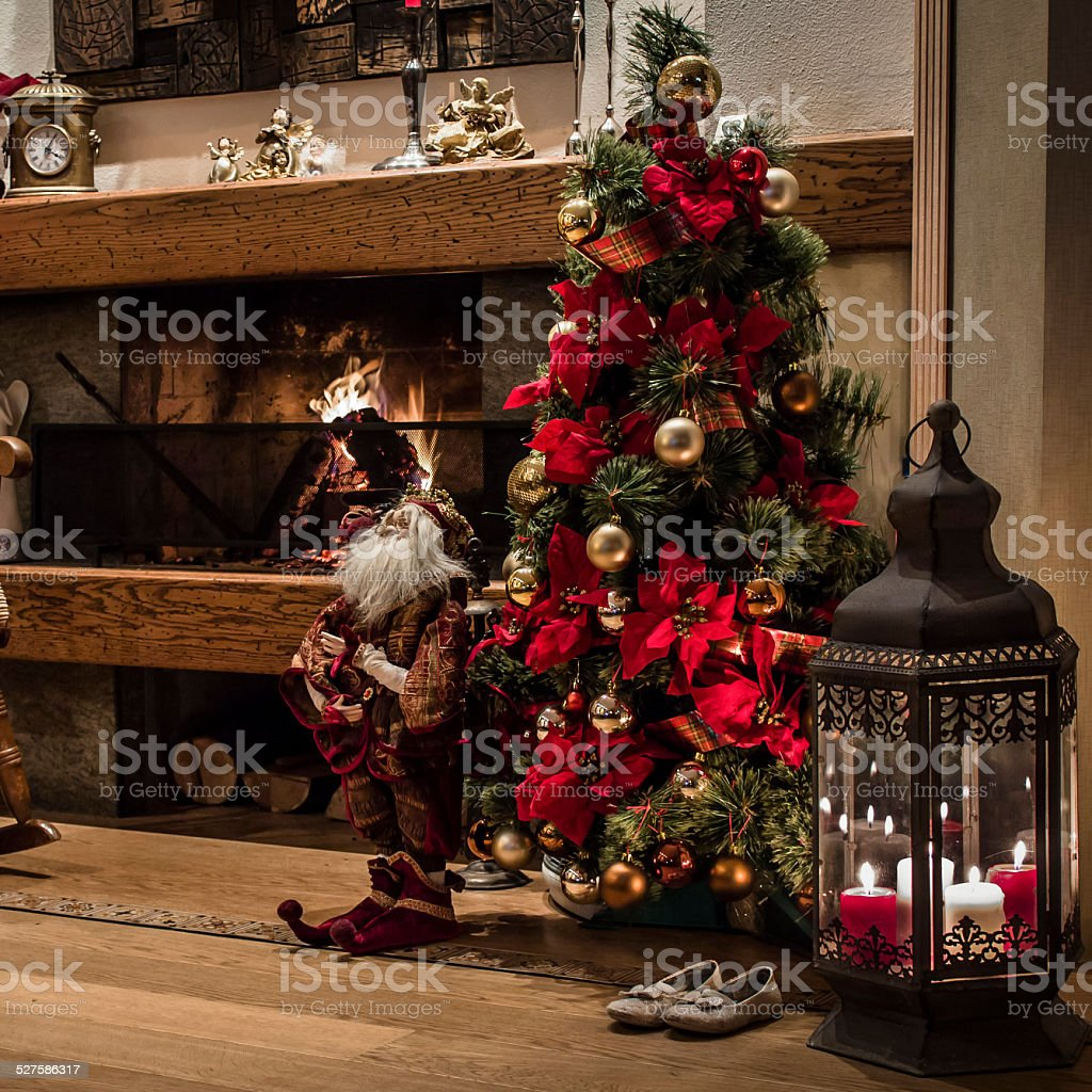 Christmas tree near fireplace with decorations stock photo