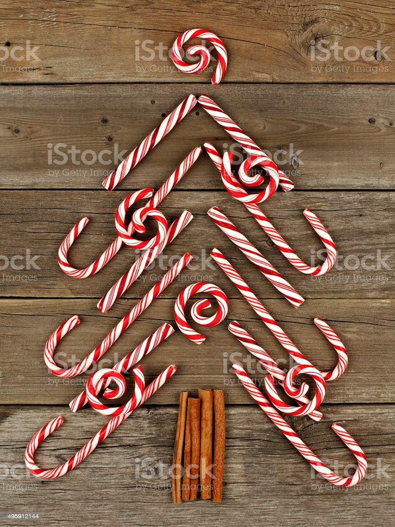 Christmas tree of candy canes and peppermint swirls over wood stock photo