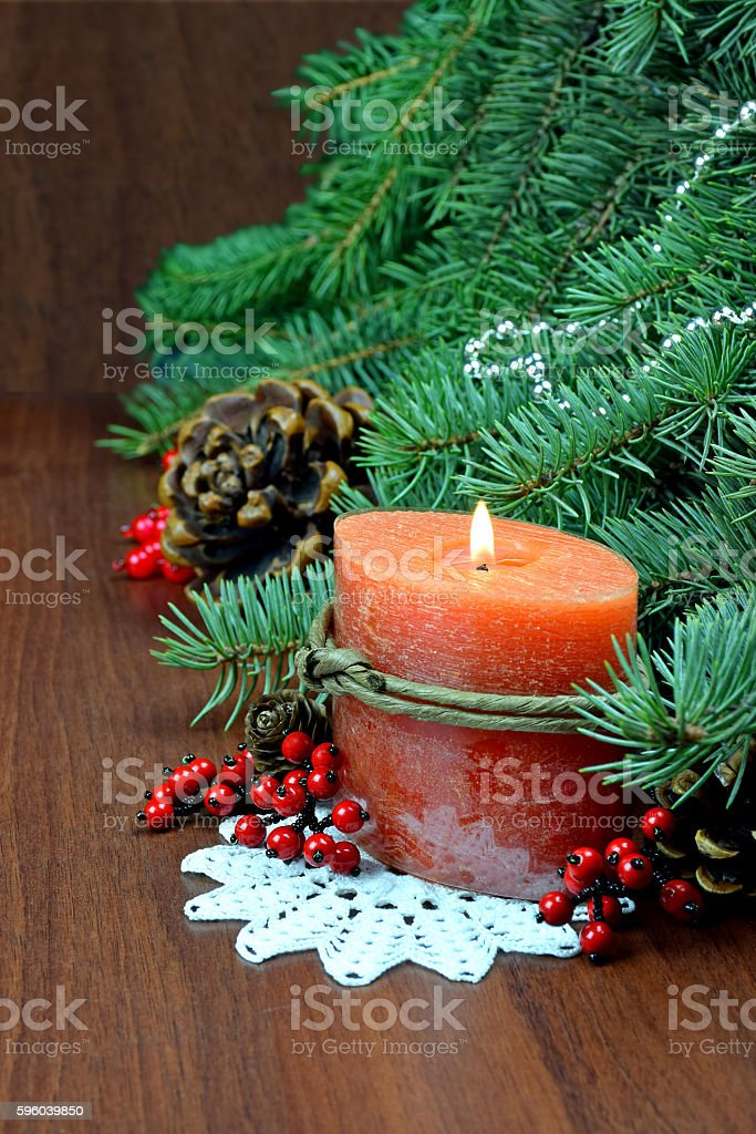 Christmas tree, red berries and cones,With a burning candle. stock photo