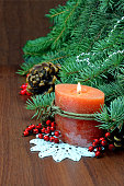 Christmas tree, red berries and cones,With a burning candle.