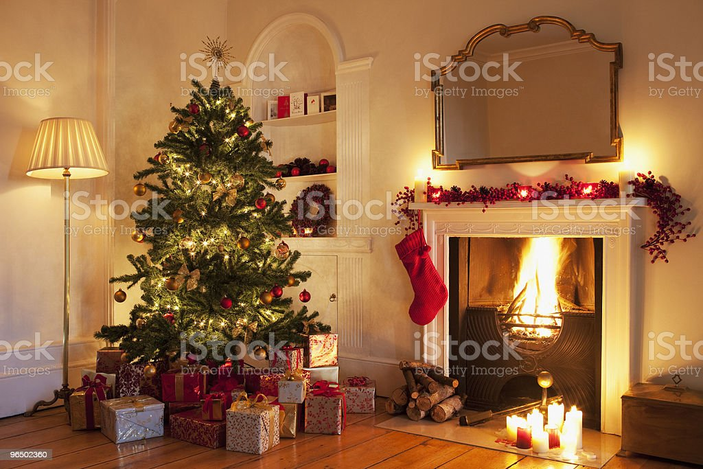 Christmas tree with gifts near fireplace stock photo