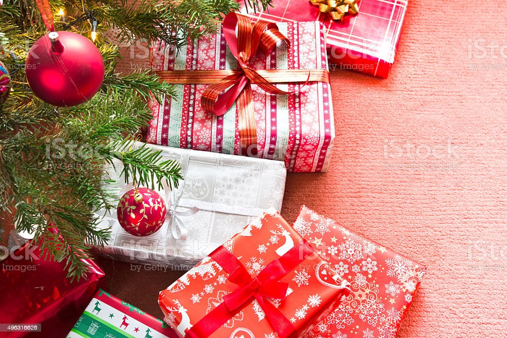 christmas tree with gifts on red carpet stock photo