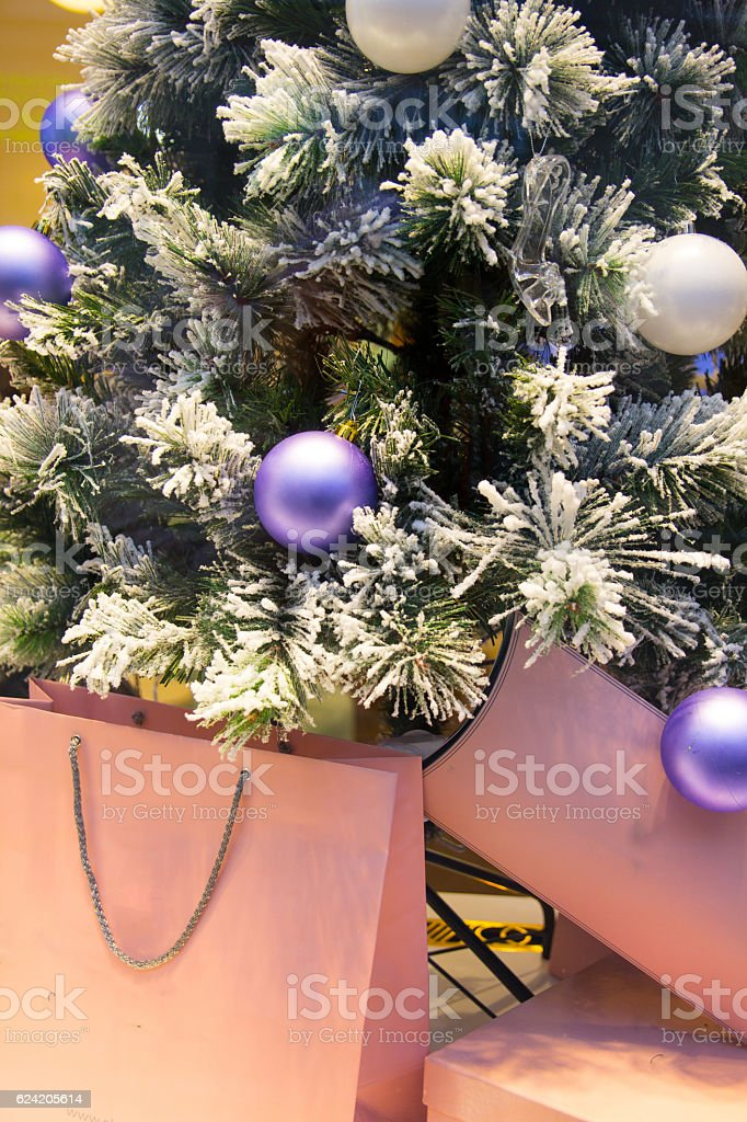 Christmas tree with purple baubles and gift bags stock photo