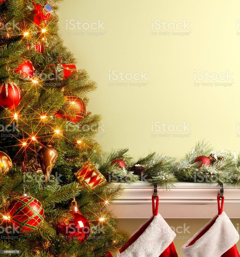 Christmas Tree With  Stockings Hung On Mantelpiece stock photo