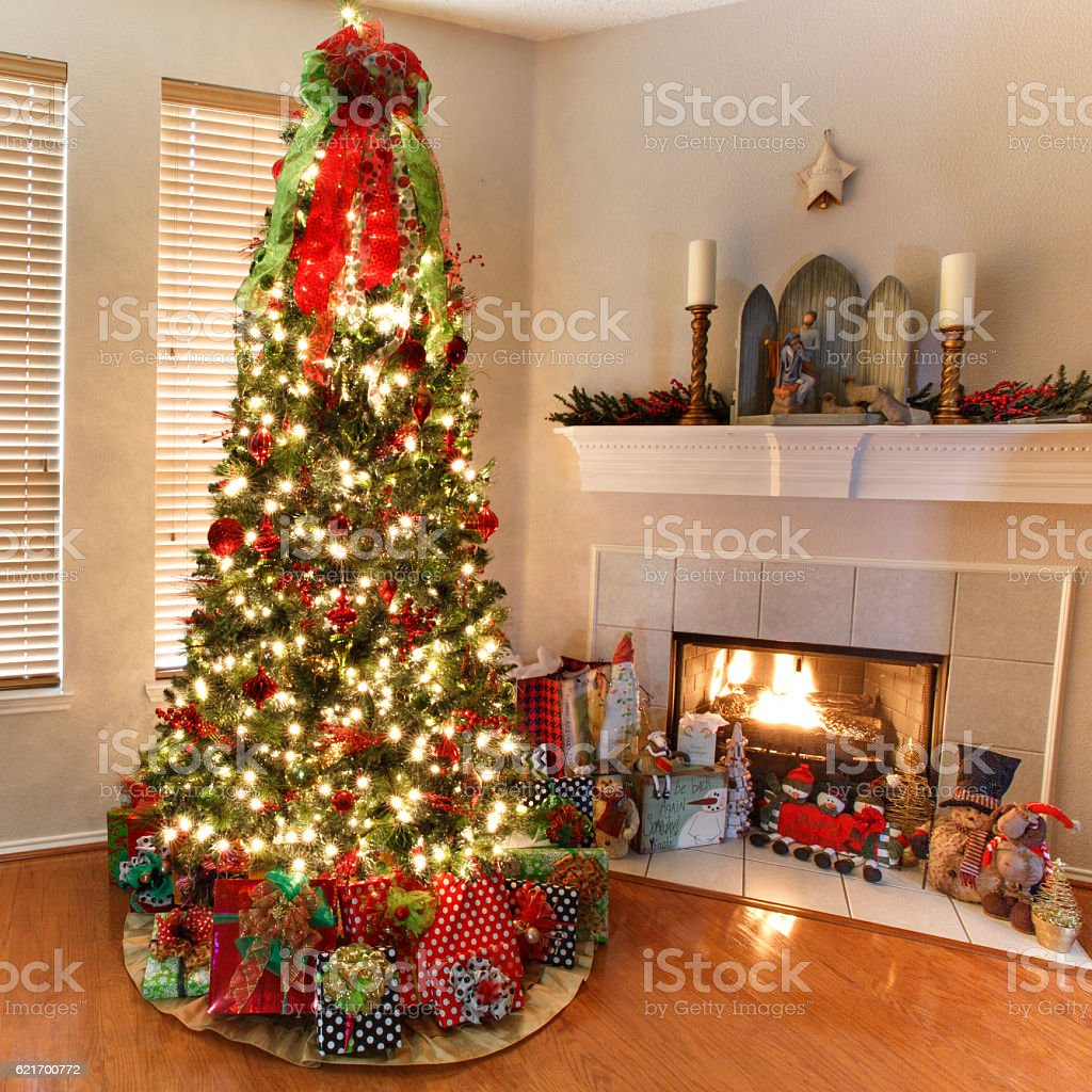 Christmas tree with wrapped gifts next to a fire place royalty-free stock photo