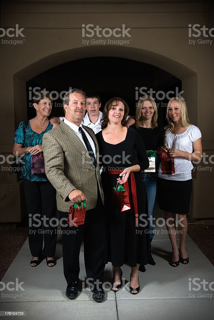 Christmas visitors walking in the driveway holding presents stock photo