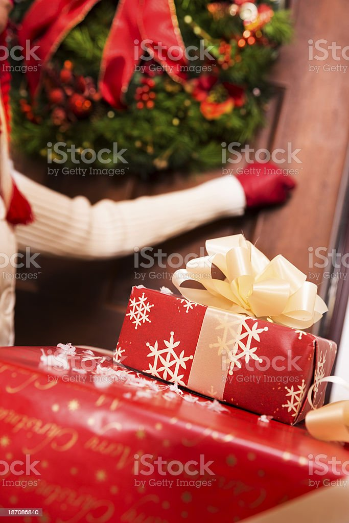 Christmas: Woman knocks on door to deliver holiday gifts. royalty-free stock photo