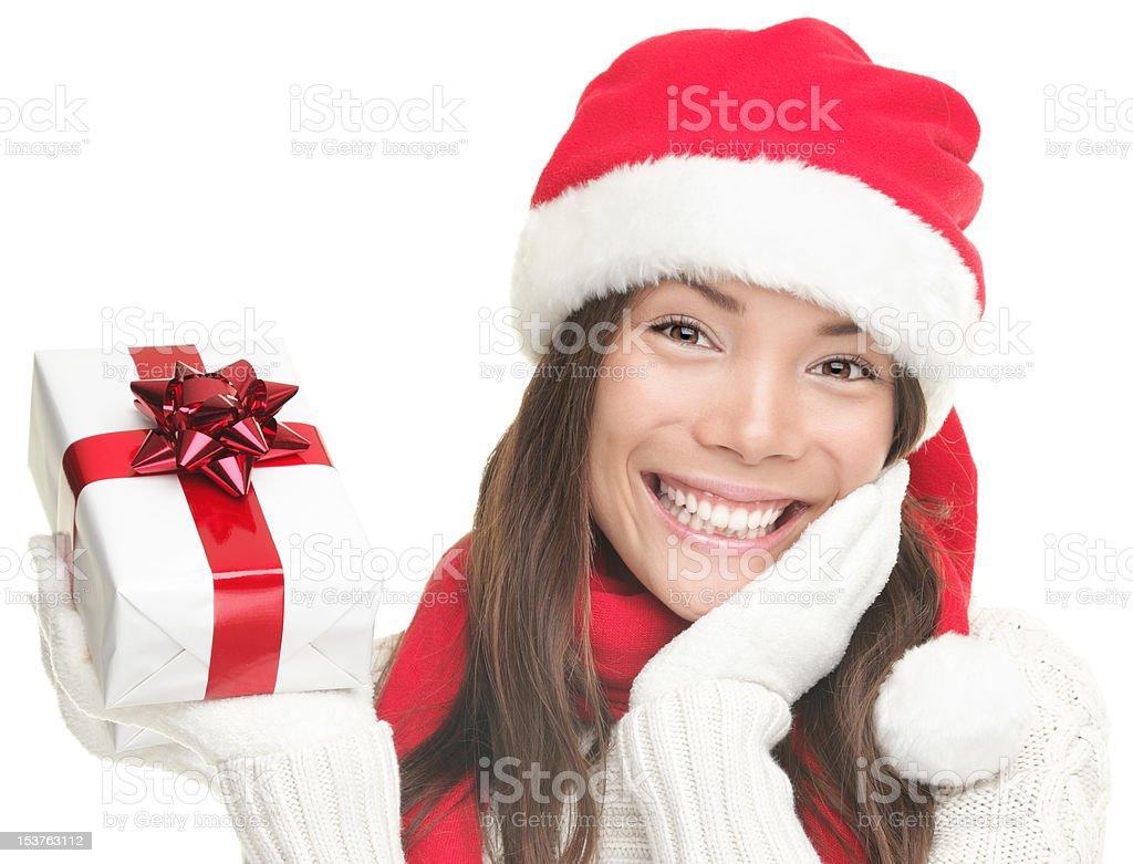 christmas woman showing gift smiling wearing santa hat royalty-free stock photo