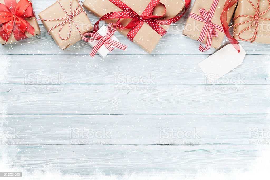 Christmas wooden background with gift boxes and snow stock photo