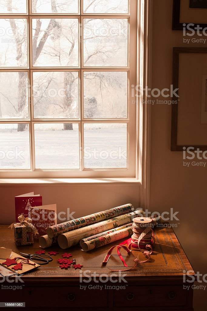 Christmas wrapping paper, ribbon, gift and cards near window royalty-free stock photo