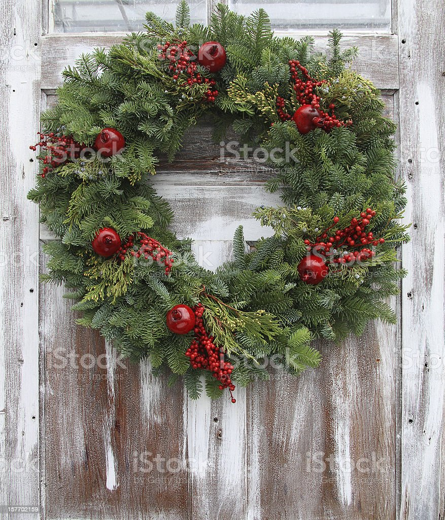 Christmas wreath hanging on a white-washed wooden door stock photo