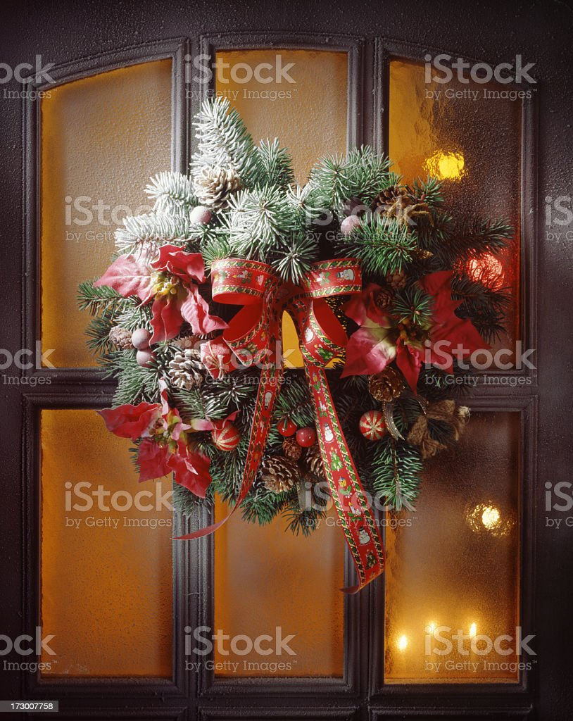A Christmas wreath hung on a wooden door with orange windows stock photo