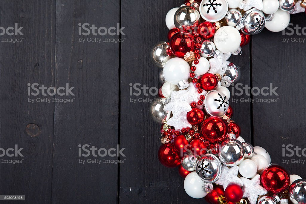 Christmas wreath with bells on dark wooden background stock photo