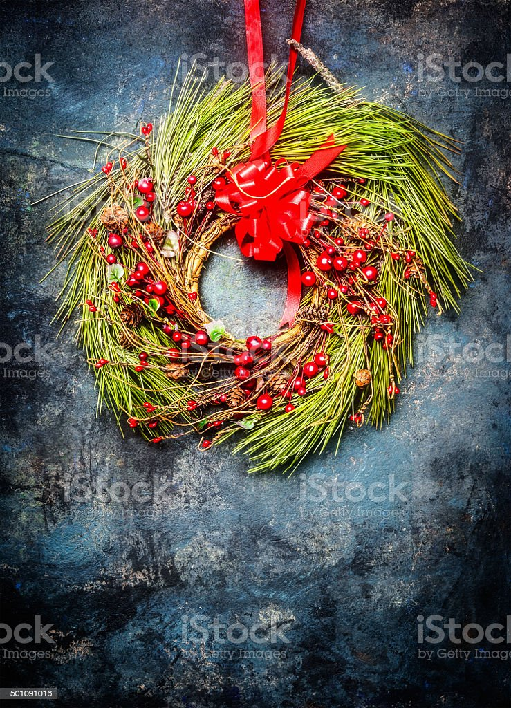 Christmas wreath with red decoration on rustic background stock photo