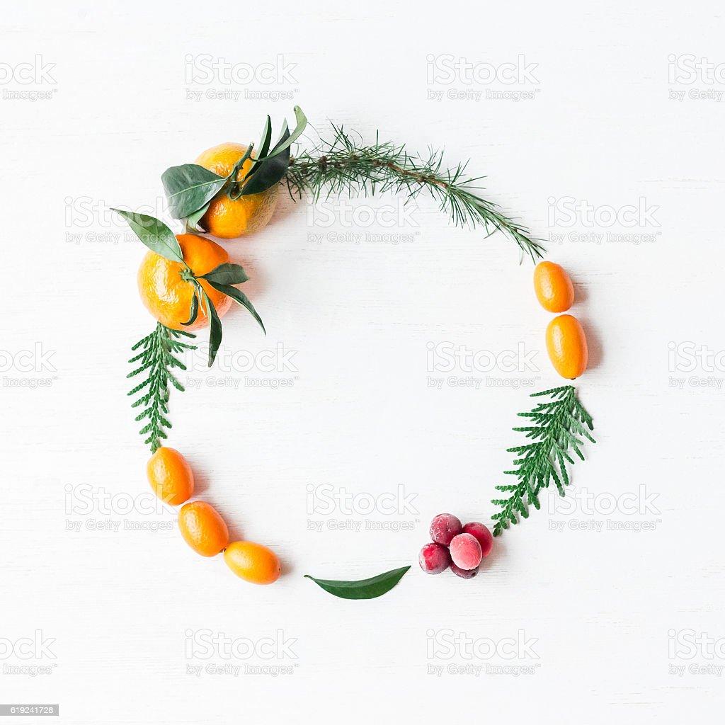 Christmas wreath with tangerines, cranberries, thuja branches, kumquats stock photo
