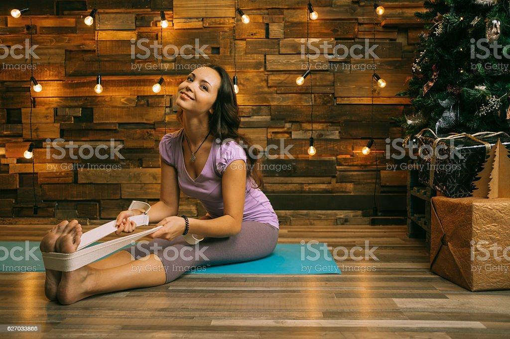 Christmas yoga. Yong woman doing yoga near fir-tree stock photo