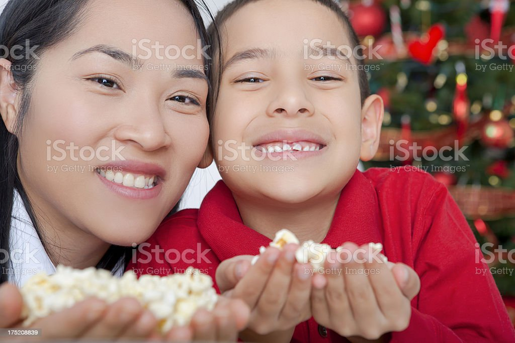 Christmas-Asian mother and son holding popcorm royalty-free stock photo