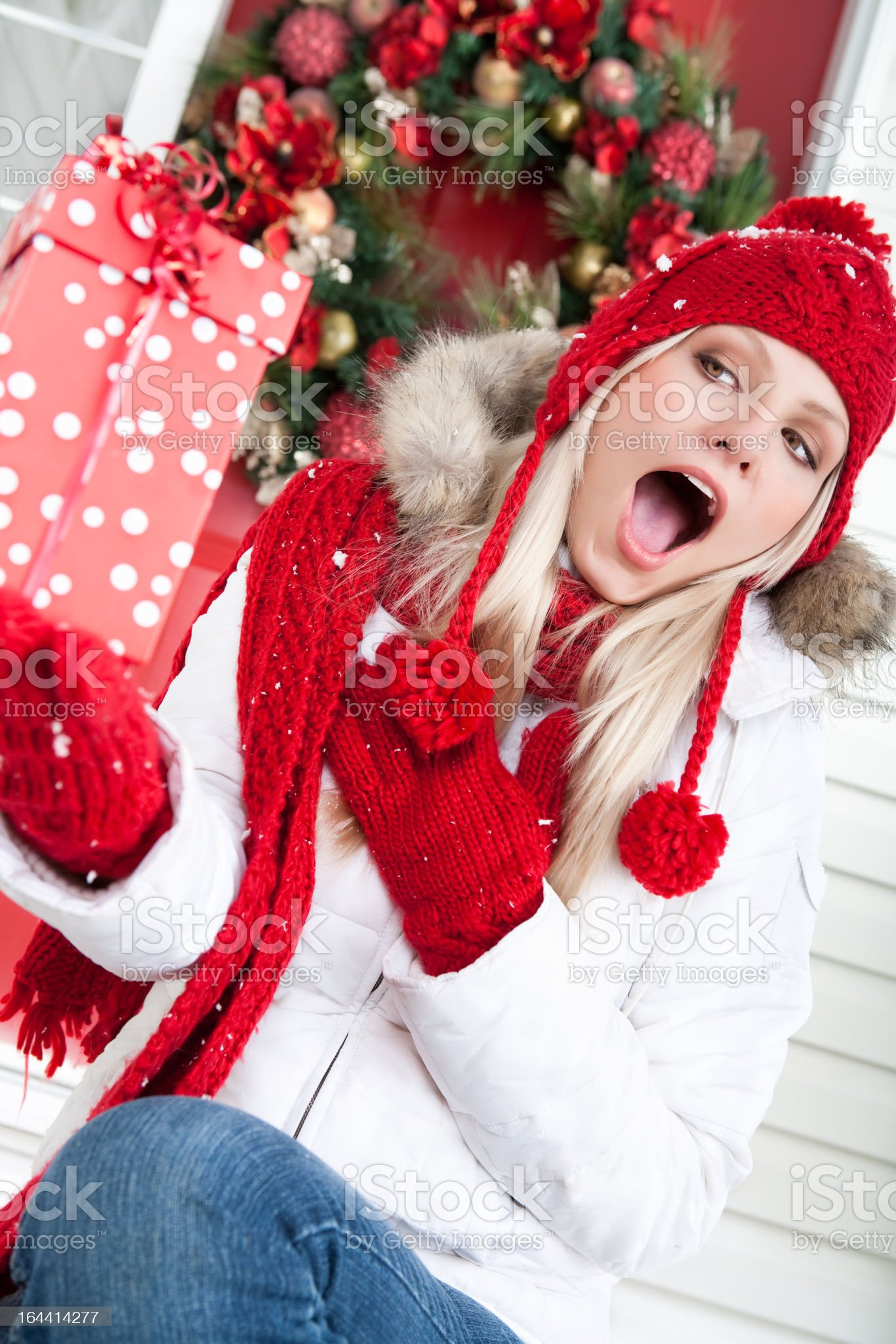 Christmas-Shocked woman holding present outside royalty-free stock photo