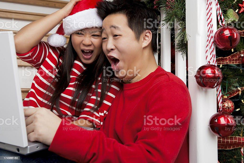 Christmas-Smiling asian couple using laptop royalty-free stock photo