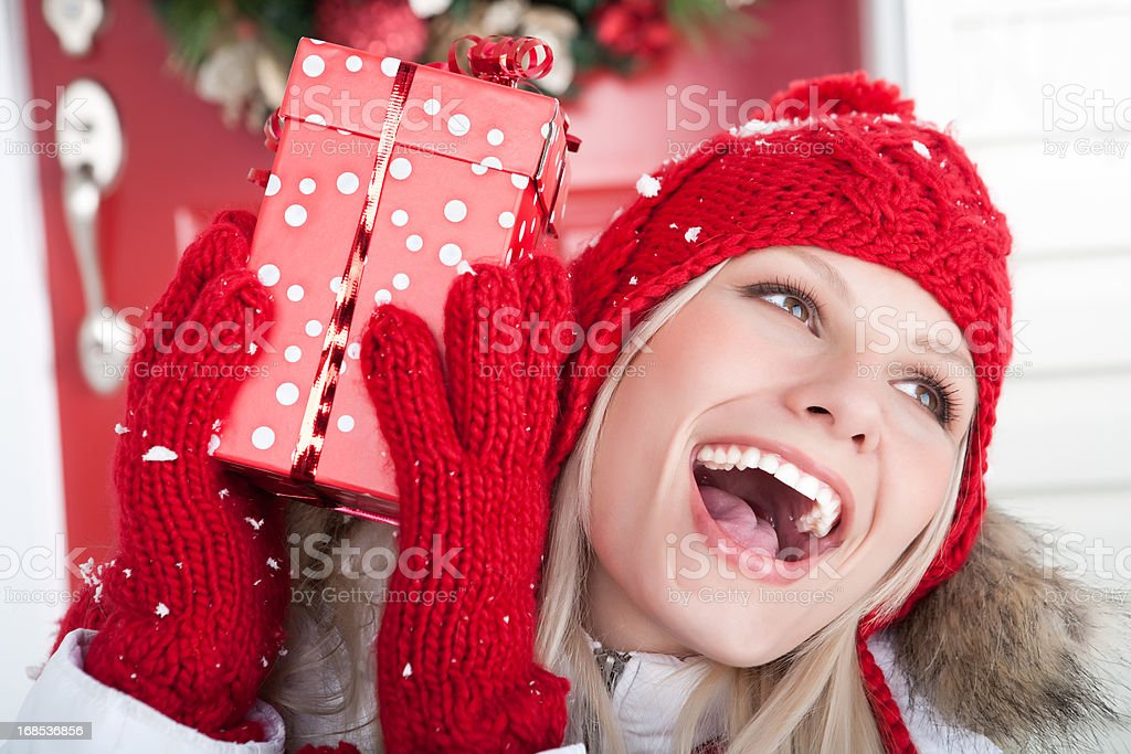 Christmas-Smiling woman holding present outside royalty-free stock photo