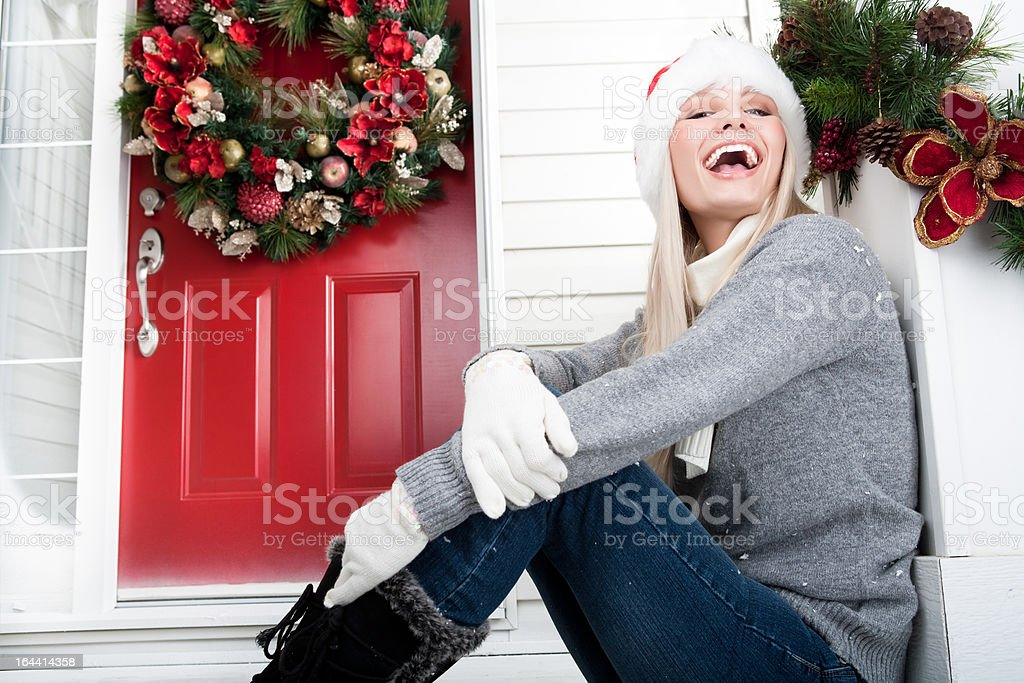 Christmas-Smiling woman sitting outside her porch royalty-free stock photo