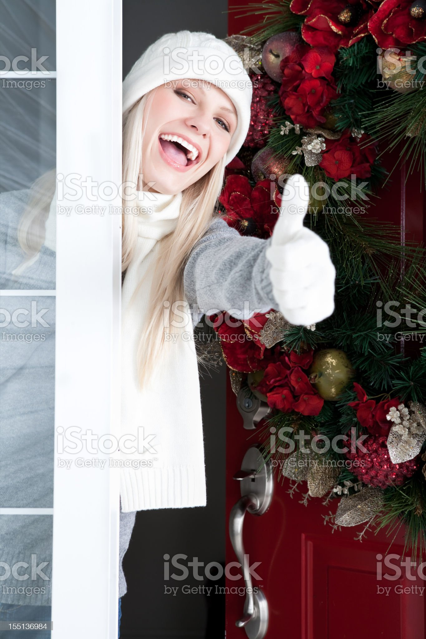 Christmas-Smiling woman with thumb up at front door royalty-free stock photo